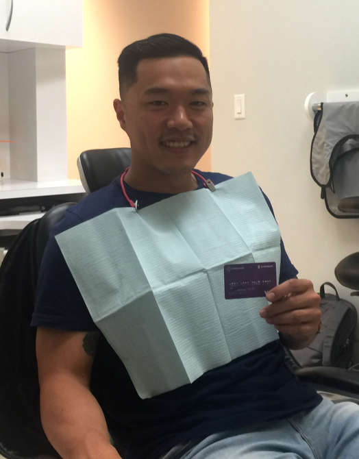 Young man sitting in a dental chair with bib on smiling while holding an Opencare visa giftcard
